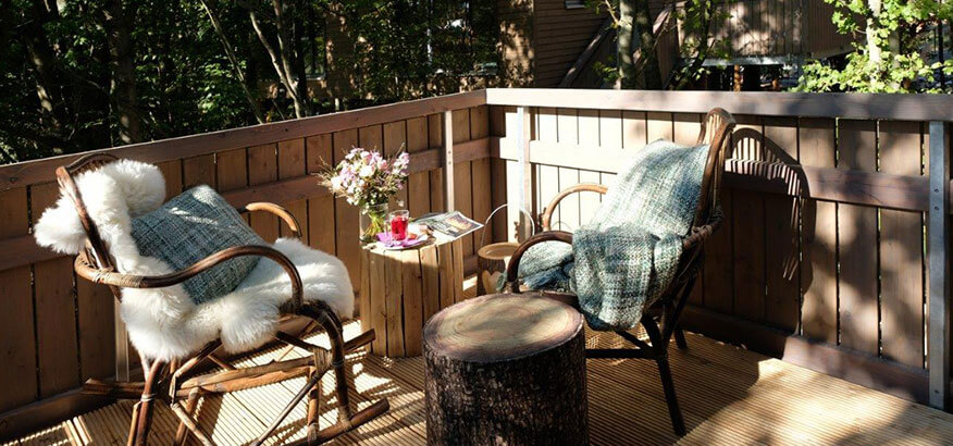 BaumChalets aussen Terrasse Schaukelstuhl Tee